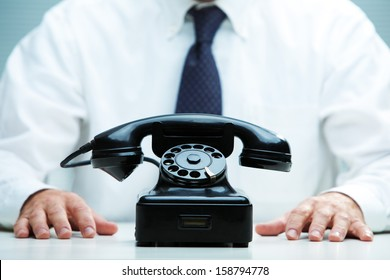 black telephone on focus with a business waiting for a call on the background