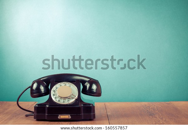 Black telephone on table in front mint green background