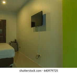 black television on green wall in hotel room