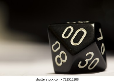 A black ten-sided die with a zero showing, on its side.