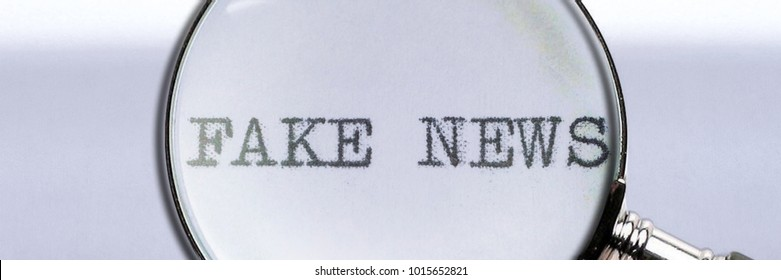Black text Fake News written on white paper