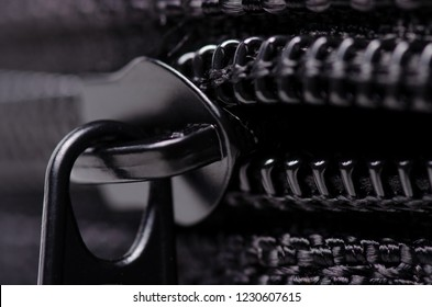 Black textile accessories material zipper metal macro on blur background