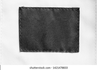 Black textile blank patch on white textile background closeup