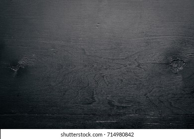 Black textured wooden background. Top view. Free space for text.