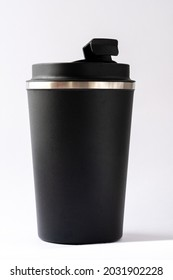 Black thermo cup or thermos mug for tea or coffee against a white background. Top slightly opened, hot beverage