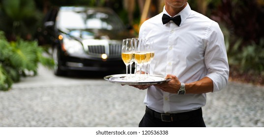 Black tie waiter serving champagne outdoors.