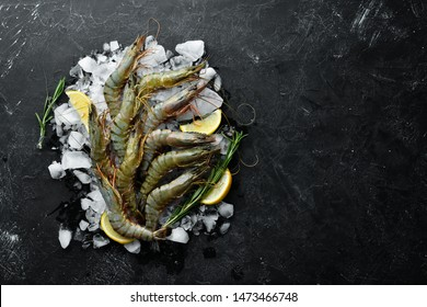 black tiger prawns with lemon on ice. Seafood. Top view. On a black background. Free copy space.