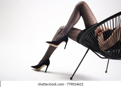 Black tights, beautiful female legs. Shapely female legs in black tights and high heels.