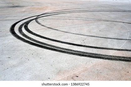 Black tire burn out tracks on a cement parking lot.