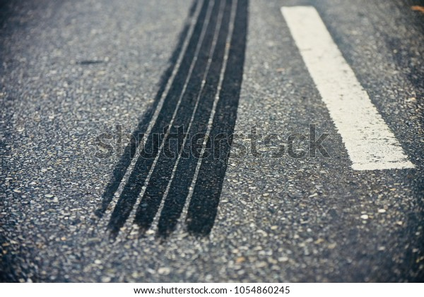 Black tire marks of a vehicle on the street isolated creative stock photo
