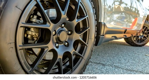 Black tire rim and disc brake of a shiny white car
