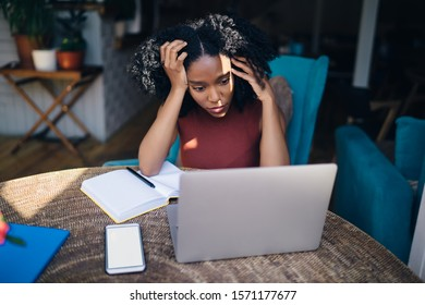 Black tired curly haired woman in casual clothes using laptop looking at problem of project leaning on hands in cafe