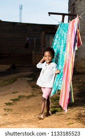 Black todder girl with her hand in her hair while standing infront of a washing line