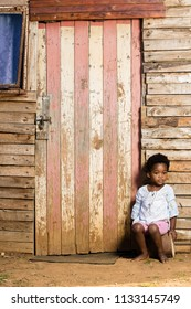 Black toddler girl infront of her house with a serious expression on her face