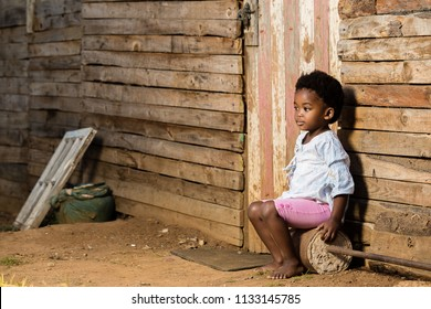 Black toddler girl sitting infront of a shack with a serious look on her face