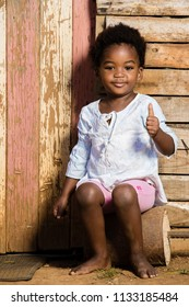 Black toddler girl sitting infront of her home with a smile on her  face