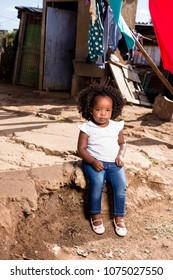 Black toddler girl sitting on a dirt step with her cute face expression.