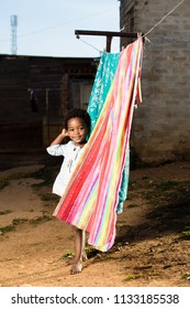 Black toddler girl standing at a washing line with a smile on her face