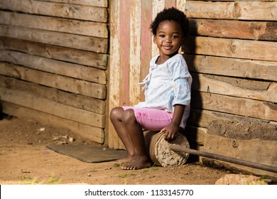 black toddler infront of her house with a smile on her face.