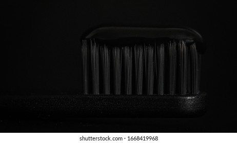 Black toothbrush and black toothpaste on black background