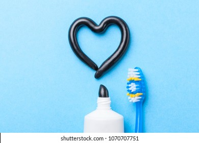Black toothpaste from charcoal for white teeth. Tooth-paste in the form of heart, tube and toothbrush on blue background.