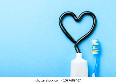 Black toothpaste from charcoal for white teeth. Tooth-paste in the form of heart, tube and toothbrush on blue background. Copy space for text