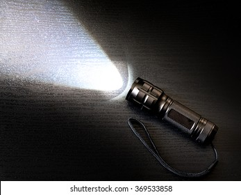 Black torch or flashlight with beam of light.