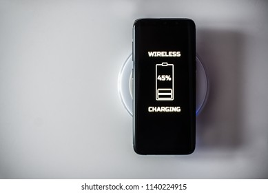 Black touchscreen smartphone wireless charging on induction charger. Wireless charger