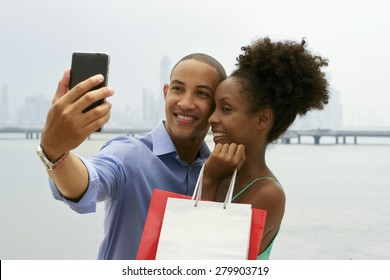 Black tourist heterosexual couple in Casco Antiguo Panama City with shopping bags. The man takes a selfie with his girlfiend and shopping bags with skyline in background