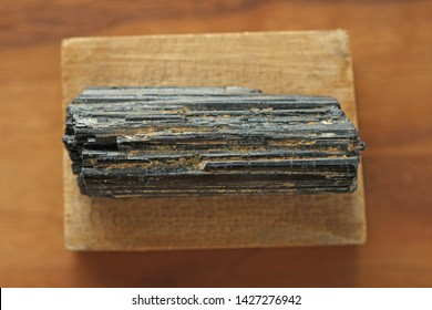 Black tourmaline stone on a background of natural wood American black walnut. Mineral collection stones. Stone is a sherl tourmaline. Black Crystal.