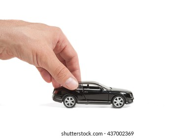 Black toy car in the men's hand on a white background. Car insurance. Automobile collision damage waiver concepts. with protective gesture and icon of car. Protection of car. Business concept.