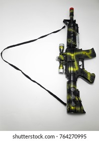 Black toy gun blends green with white backdrop.Isolate.