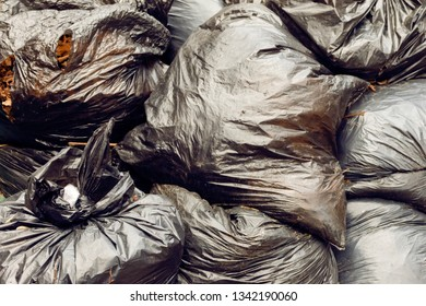 Black Trash Bags Litter Garbage close-up background. Plastic Bags pile junk garbage Trash texture