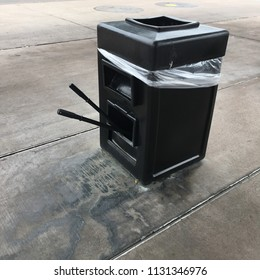 Black Trash Can with Window Washer Wands at Gas Station
