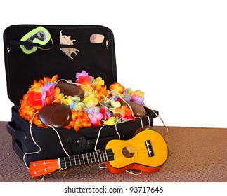 Black travel case full of vacation treasures.  Ukulele, coconut bra, leis and seashells.  White copy space.