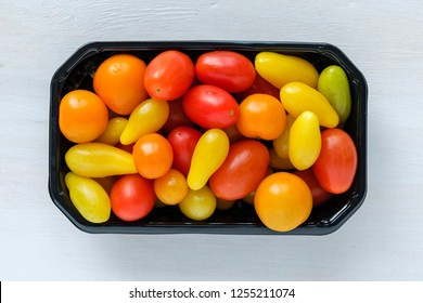 Black tray of fresh homegrown tomatoes of different colors, viewed from above on white wooden background