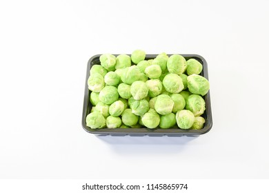 Black tray full with green fresh raw brussel sprout cabbage from garden nature, organic vegetable full witamin and healthy on isolated white background, package for sale in supermaket.