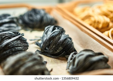Black trend Fettuccine round nests. Various mix of uncooked pasta in on wooden tray in the shop window. Different kind of dry macaroni in round form. Italian foods concept of spaghetti and menu design