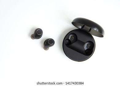Black true wireless earbuds with power bank case on the white isolated background