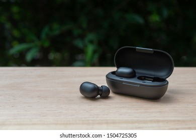 Black true wireless earbuds with power bank case on the wooden table with green background