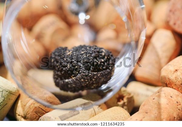 Black Truffle in an empty glass on wine stoppers.