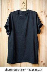 Black t-shirt hang on wood wall.