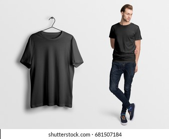Black t-shirt on a man in jeans,isolated, mockup. Hanging blank t-shirt, against empty wall.