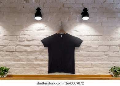 Black T-Shirt on a wall with projectors. Mockup for your prints.