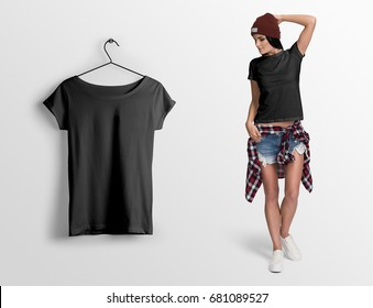 Black t-shirt on a young woman in shorts, hat and checked shirt, isolated, mockup. Hanging black blank t-shirt, against empty wall.
