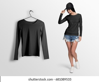Black t-shirt wide neck, long sleeves, on a young woman in shorts and cap, isolated mockup. Hanging t-shirt long sleeves, against empty wall background.