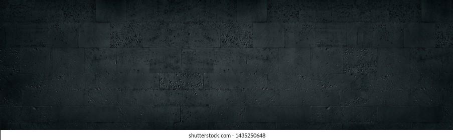 Black tuff brick wall wide texture. Dark rough stone block masonry panoramic background