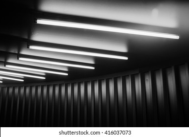 Black tunnel ceiling with fluorescent lamps.