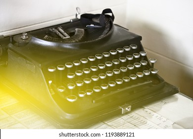 Black typewriter on table.A mechanical man made to replace handwriting. Looks like a keyboard.
