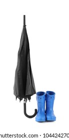 Black umbrella and gumboots on white background